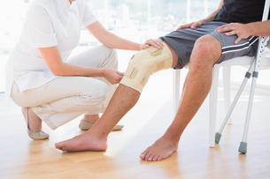 Doctor examining her patient kneeの写真素材 [FYI00005986]