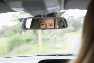 Young woman in the drivers seat looking in the mirrorの素材 [FYI00005993]