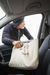 Thief breaking into car and stealing hand bagの写真素材 [FYI00005996]