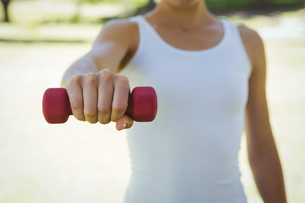 Fit woman lifting dumbbell in parkの素材 [FYI00006012]
