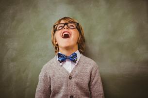 Boy laughing in front of blackboardの写真素材 [FYI00006022]