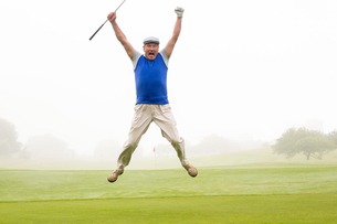 Excited golfer jumping up and smiling at cameraの写真素材 [FYI00006032]