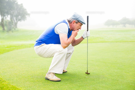 Serious golfer kneeling on the putting greenの素材 [FYI00006041]