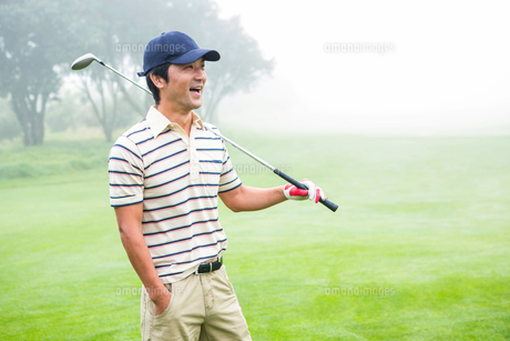 Smiling golfer standing and holding his clubの素材 [FYI00006050]