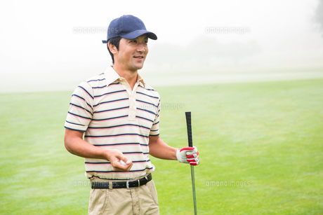 Cheerful golfer holding his club and golf ballの素材 [FYI00006051]