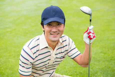 Crouching golfer smiling at camera and holding clubの素材 [FYI00006057]