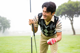 Golfer holding golf ball and clubの素材 [FYI00006064]