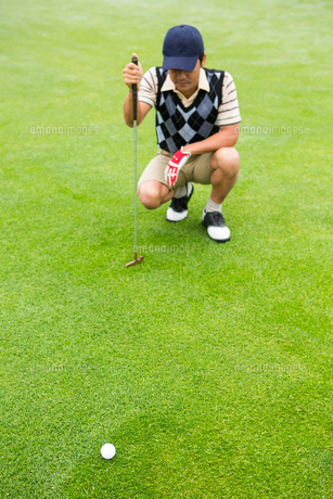 Crouching golfer looking at the ballの写真素材 [FYI00006066]