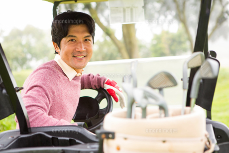 Happy golfer driving his golf buggy smiling at cameraの写真素材 [FYI00006067]