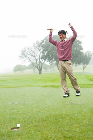 Excited golfer cheering on putting greenの素材 [FYI00006068]