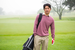 Golfer standing holding his golf bagの写真素材 [FYI00006070]
