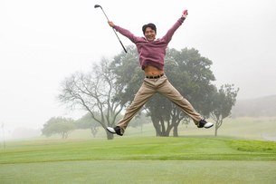 Excited golfer jumping up and smiling at cameraの写真素材 [FYI00006071]