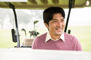 Happy golfer driving his golf buggyの素材 [FYI00006073]