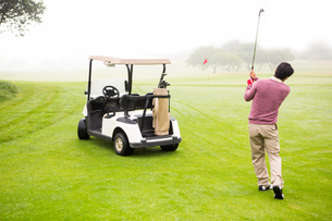 Golfer teeing off next to his golf buggyの素材 [FYI00006076]