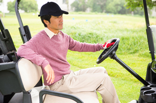 Golfer driving his golf buggyの素材 [FYI00006077]