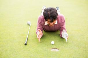 Golfer lying near golf ballの素材 [FYI00006078]
