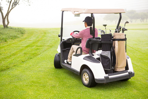 Golfer driving in his golf buggyの素材 [FYI00006079]