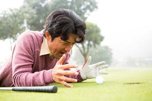 Golfer lying near golf ballの素材 [FYI00006080]