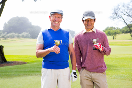 Golfing friends holding cups smiling at cameraの素材 [FYI00006084]