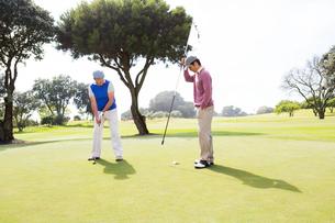 Golfer swinging his club with friendの写真素材 [FYI00006087]