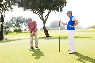 Golfer swinging his club with friendの写真素材 [FYI00006090]