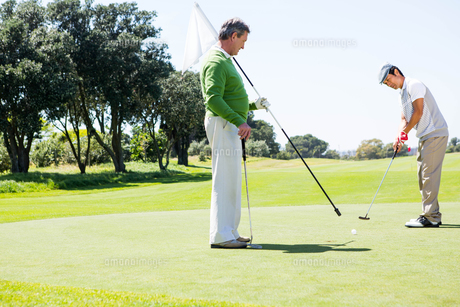 Golfer holding hole flag for friend putting ballの素材 [FYI00006093]