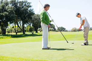Golfer holding hole flag for friend putting ballの写真素材 [FYI00006093]