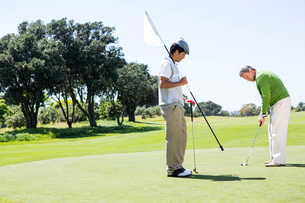 Golfer holding hole flag for friend putting ballの写真素材 [FYI00006094]