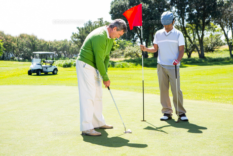 Golfer holding hole flag for friend putting ballの素材 [FYI00006095]