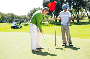 Golfer holding hole flag for friend putting ballの写真素材 [FYI00006095]