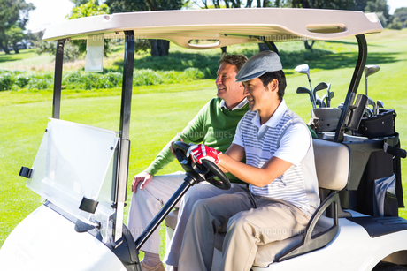 Golfing friends laughing together in their golf buggyの素材 [FYI00006098]