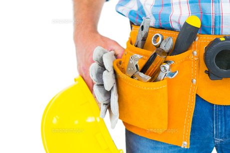 Manual worker wearing tool belt while holding gloves and helmetの写真素材 [FYI00006124]