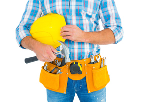 Manual worker wearing tool belt while holding hammer and helmetの写真素材 [FYI00006128]