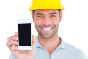 Portrait of smiling handyman showing smart phoneの素材 [FYI00006135]