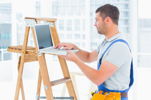 Handyman using laptop by ladder in bright officeの写真素材 [FYI00006139]