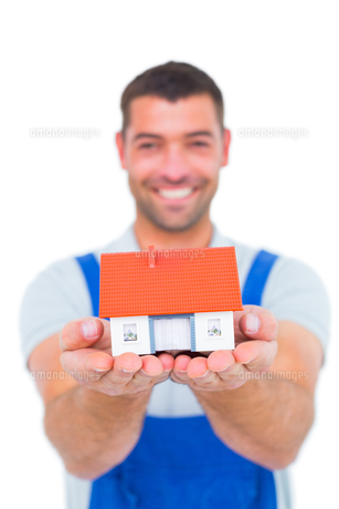 Portrait of happy handyman holding house modelの写真素材 [FYI00006141]