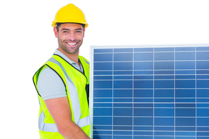 Smiling handyman in protective clothing carrying solar panelの写真素材 [FYI00006148]