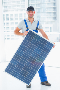 Manual worker holding solar panel in bright officeの写真素材 [FYI00006151]