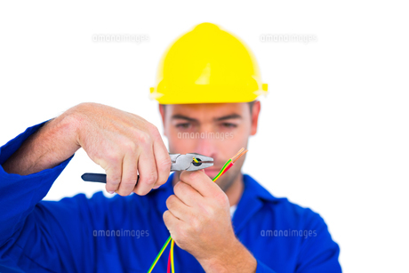 Electrician wearing hard hat while cutting wire with pliersの写真素材 [FYI00006156]