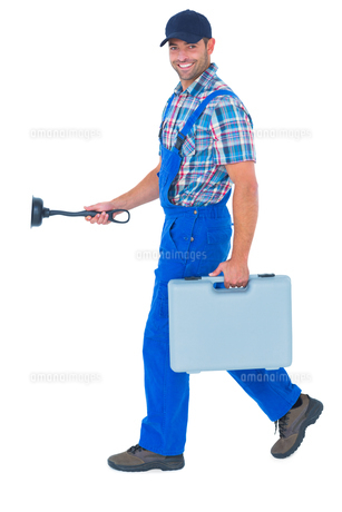Happy plumber with plunger and toolbox walking on white backgroundの写真素材 [FYI00006157]