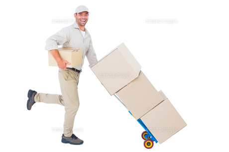 Happy delivery man with trolley of boxes running on white backgroundの写真素材 [FYI00006165]