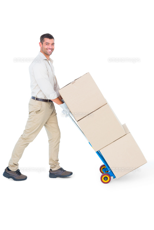 Happy delivery man pushing trolley of boxesの写真素材 [FYI00006166]