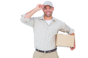 Portrait of happy delivery man with cardboard box wearing capの写真素材 [FYI00006176]
