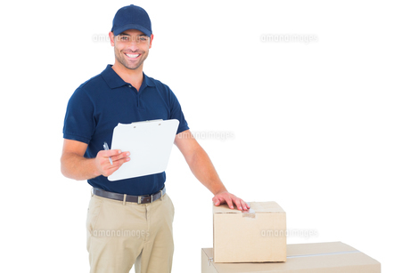 Happy delivery man with cardboard boxes and clipboardの写真素材 [FYI00006178]