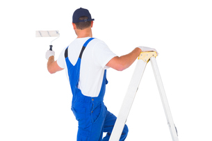 Handyman climbing ladder while using paint rollerの写真素材 [FYI00006180]