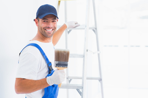 Happy handyman with paintbrush while climbing ladderの写真素材 [FYI00006186]