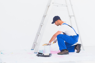 Side view of handyman in overalls opening paint canの写真素材 [FYI00006187]