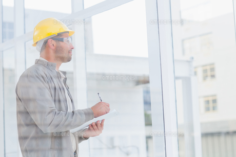 Architect writing on clipboard while looking through office windowの素材 [FYI00006190]
