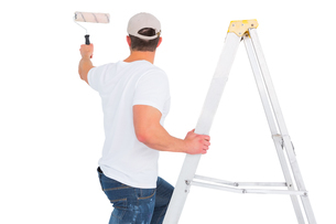 Handyman climbing ladder while using paint rollerの写真素材 [FYI00006195]