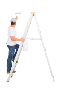 Handyman climbing ladder while using paint rollerの写真素材 [FYI00006199]